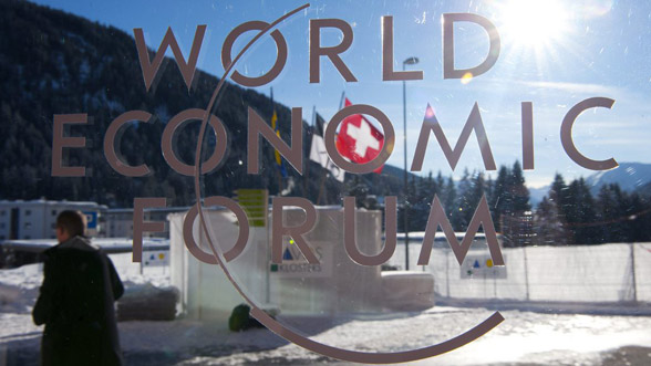 """Participant walks behind a logo of the World Economic Economic Forum at the 41st Annual Meeting of the World Economic Forum, WEF, in Davos, Switzerland, Thursday, January 27, 2011. The overarching theme of the World Economic Forum, WEF, annual meeting is """"Shared Norms for the New Reality"""". It takes place from January 26 to 30. (KEYSTONE/Laurent Gillieron).."""